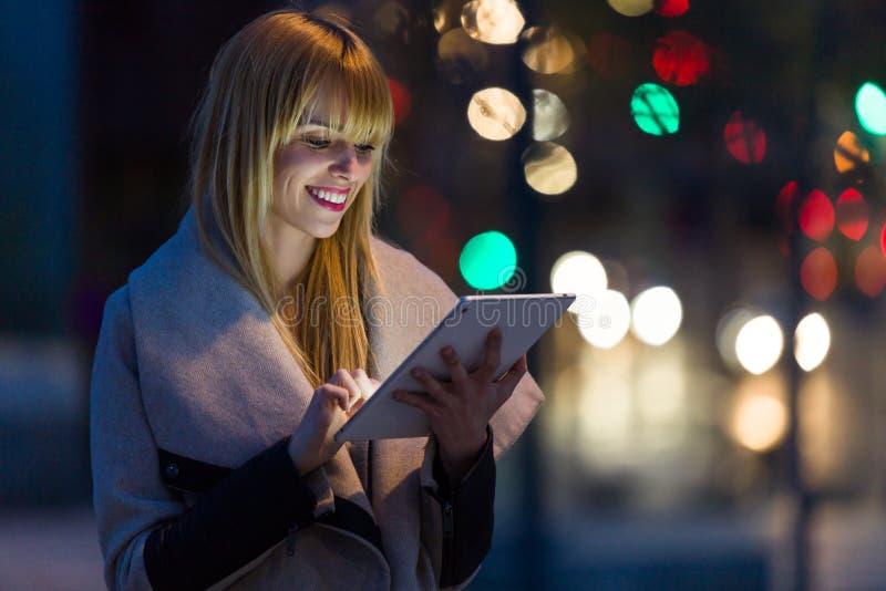 Jolie jeune femme à l'aide de son comprimé numérique dans la rue la nuit photos stock