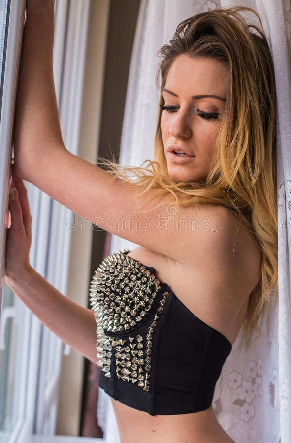 Jolie jeune femme à la fenêtre photo stock