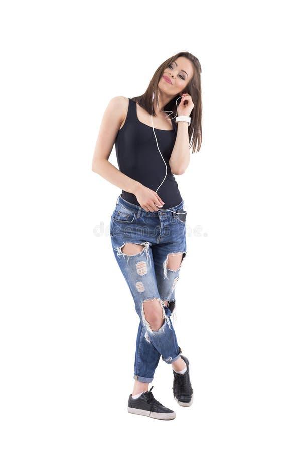 Jolie jeune femme écoutant la musique sur des écouteurs fixés au téléphone portable dans la poche photos stock