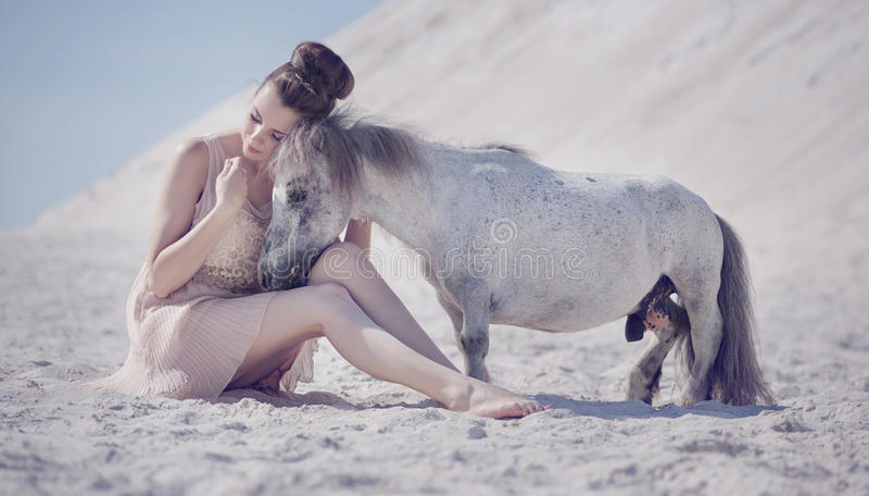 Jolie jeune femme étreignant le poney photographie stock