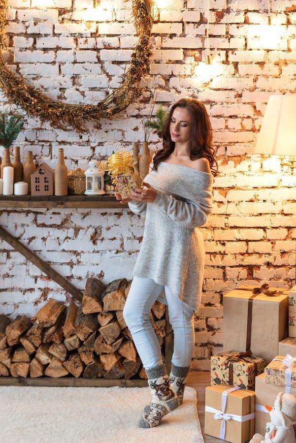 Jolie jeune femme apaisée regardant une position de boîte-cadeau près d'un tas de bois dans une rétro salle année décorée de cru  photos stock