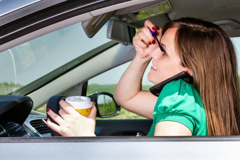 Jolie jeune femme appliquant le maquillage, parlant du téléphone et du drinki image libre de droits