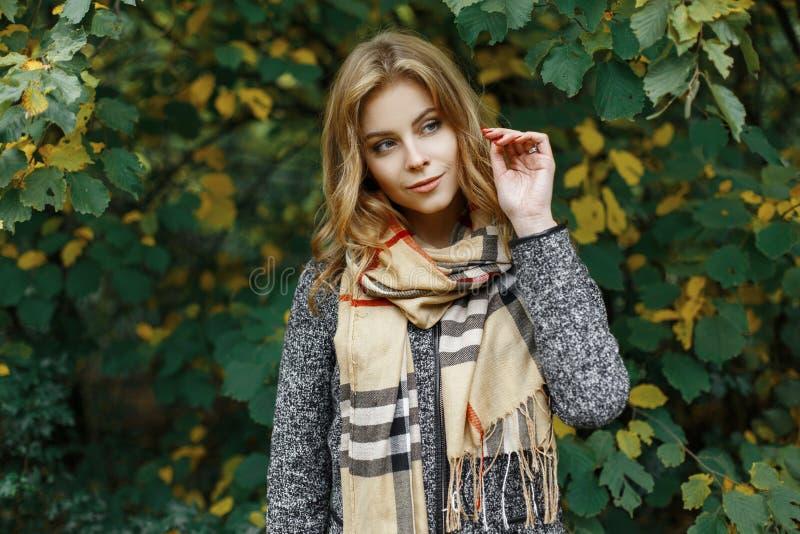 Jolie jeune femme attirante avec des yeux bleus dans une écharpe de vitage dans un manteau élégant en parc photographie stock
