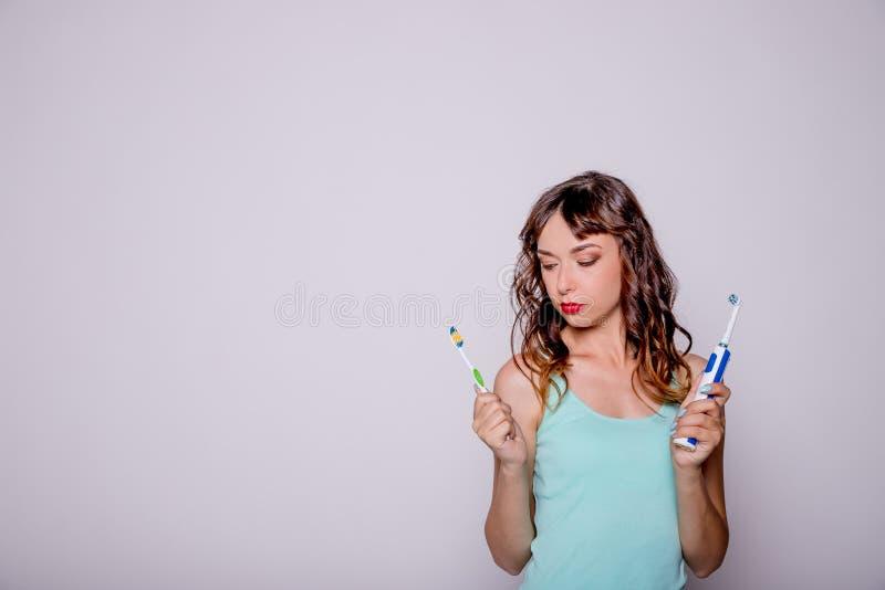 Jolie jeune femme avec des brosses à dents La femme heureuse, belle fille de sourire avec de longs cheveux bouclés choisit la bro images libres de droits