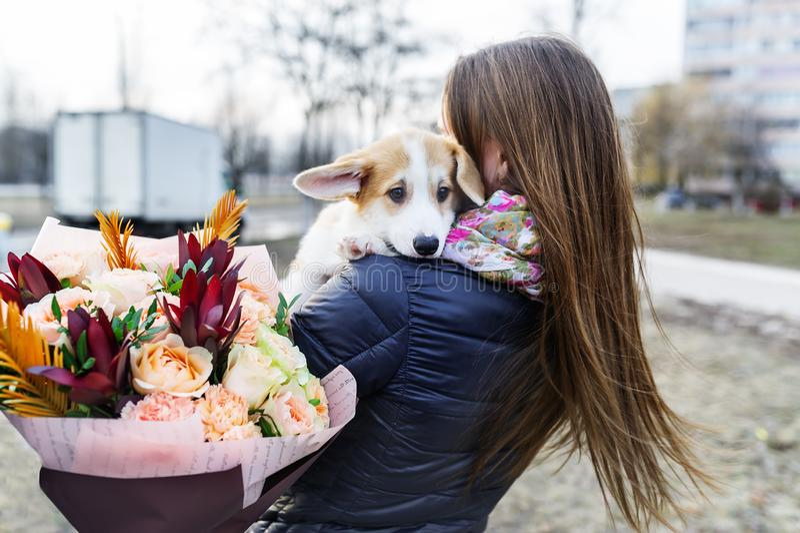 Jolie jeune femme avec le bouquet des fleurs tenant le petit chien, sur le fond de la rue de ville Vue arri?re photo stock