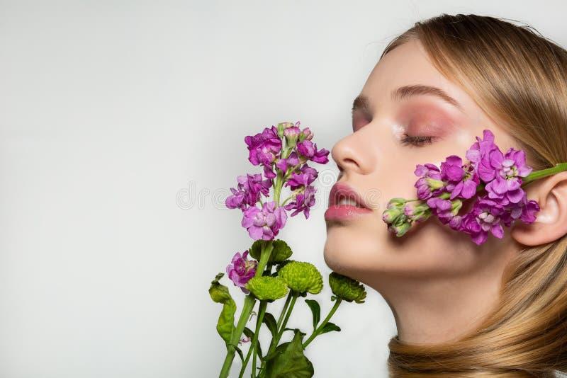 Jolie jeune femme avec le regard frais de ressort, cheveux merveilleux, maquillage gentil, fleurs pr?s de son visage et dans les  photographie stock