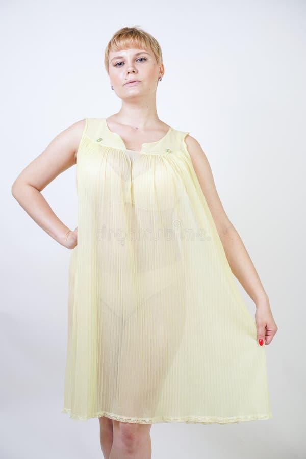 Jolie jeune femme avec les cheveux courts et corps potelé utilisant la chemise de nuit transparente et posant sur seul le fond bl photo stock