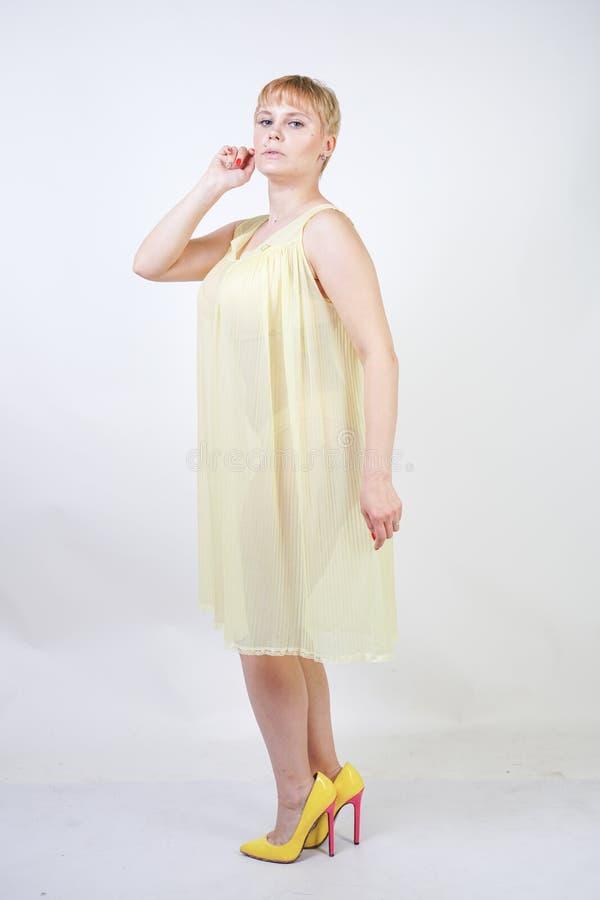 Jolie jeune femme avec les cheveux courts et corps potelé utilisant la chemise de nuit transparente et posant sur seul le fond bl image stock