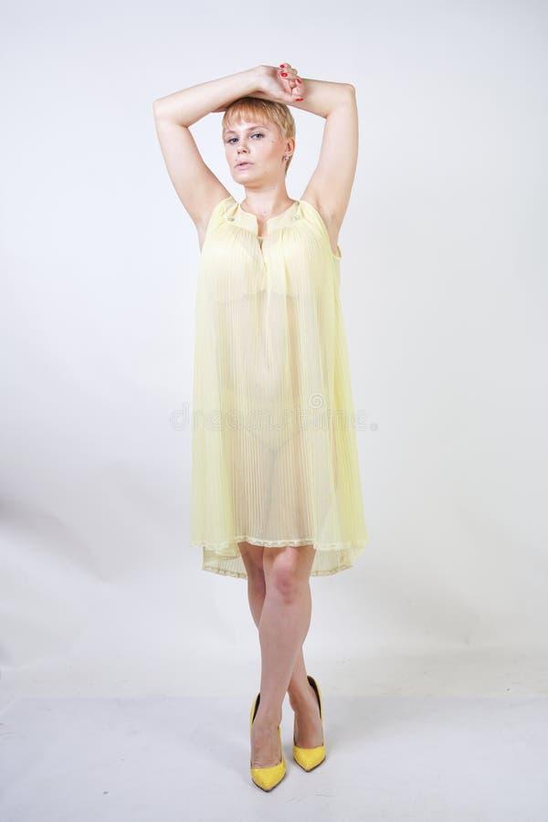 Jolie jeune femme avec les cheveux courts et corps potelé utilisant la chemise de nuit transparente et posant sur seul le fond bl photos stock