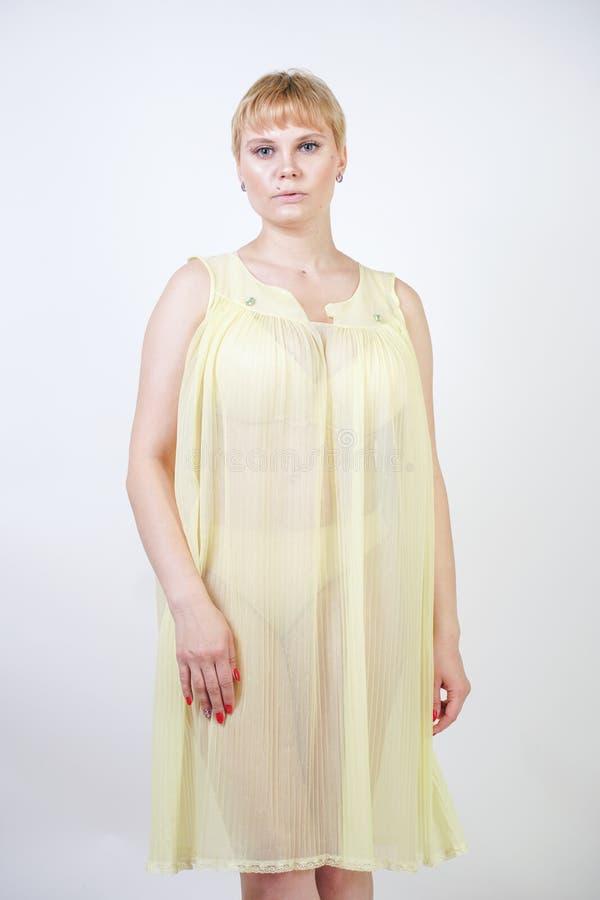 Jolie jeune femme avec les cheveux courts et corps potelé utilisant la chemise de nuit transparente et posant sur seul le fond bl photo libre de droits