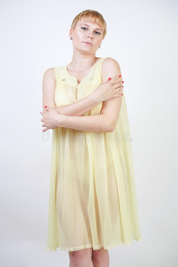 Jolie jeune femme avec les cheveux courts et corps potelé utilisant la chemise de nuit transparente et posant sur seul le fond bl photographie stock