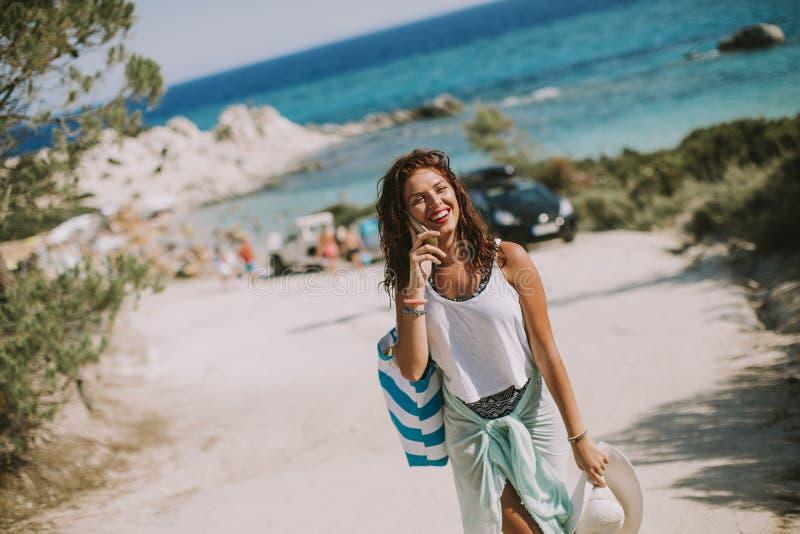 Jolie jeune femme avec un sac utilisant le t?l?phone portable sur la plage photographie stock libre de droits