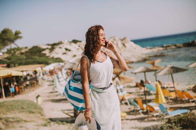 Jolie jeune femme avec un sac utilisant le t?l?phone portable sur la plage photographie stock