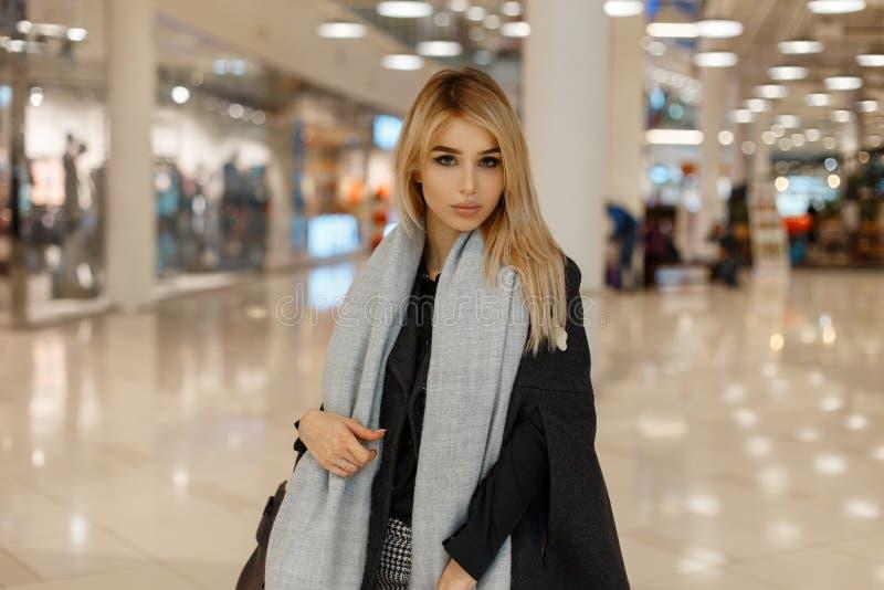 Jolie jeune femme blonde élégante fascinante dans un manteau à la mode luxueux de cru de cru avec une écharpe chaude à la mode gr images stock