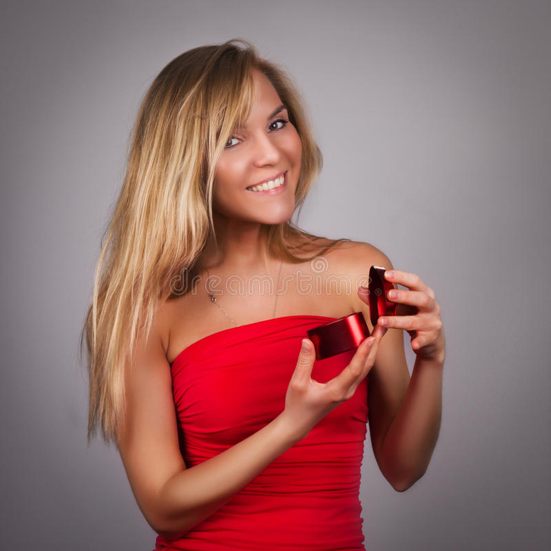 Jolie jeune femme blonde avec Valentine actuel dans des mains en Re photo libre de droits