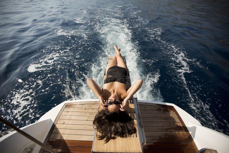 Jolie jeune femme détendant sur le yacht photos stock