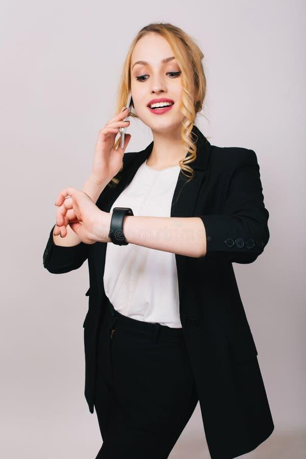 Jolie jeune femme d'affaires joyeuse dans le costume de bureau parlant au téléphone, souriant et regardant la montre sur le fond  photographie stock