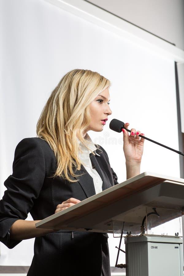 Jolie jeune femme d'affaires qui fait une présentation lors d'une conférence photographie stock