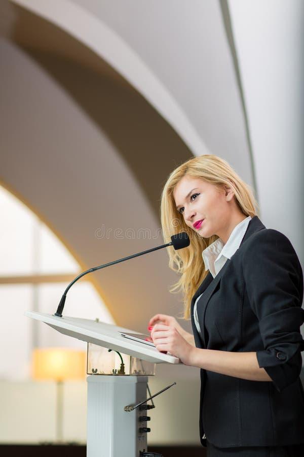 Jolie jeune femme d'affaires qui fait une présentation lors d'une conférence images libres de droits