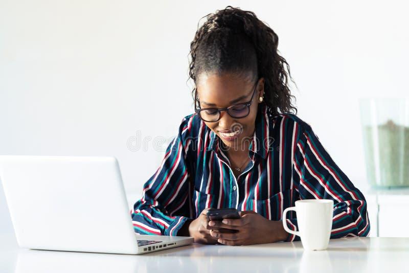 Jolie jeune femme d'affaires utilisant son smartphone tout en travaillant avec l'ordinateur portable dans le bureau photo stock