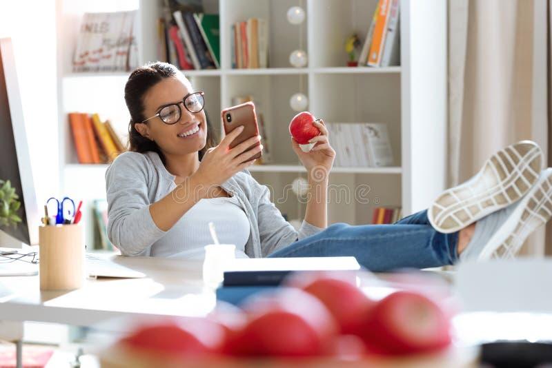 Jolie jeune femme d'affaires utilisant son téléphone portable tout en mangeant la pomme rouge dans le bureau photographie stock libre de droits