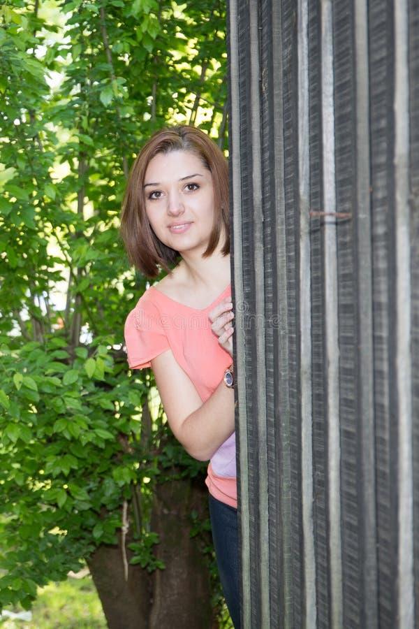Jolie jeune femme d'amusement derrière le jeu en bois de hutte frais images libres de droits