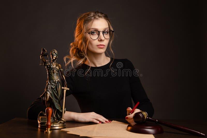 Jolie jeune femme dans des verres et dans un document se reposant et wrighting noir de robe d'importaint, femme de notaire images libres de droits