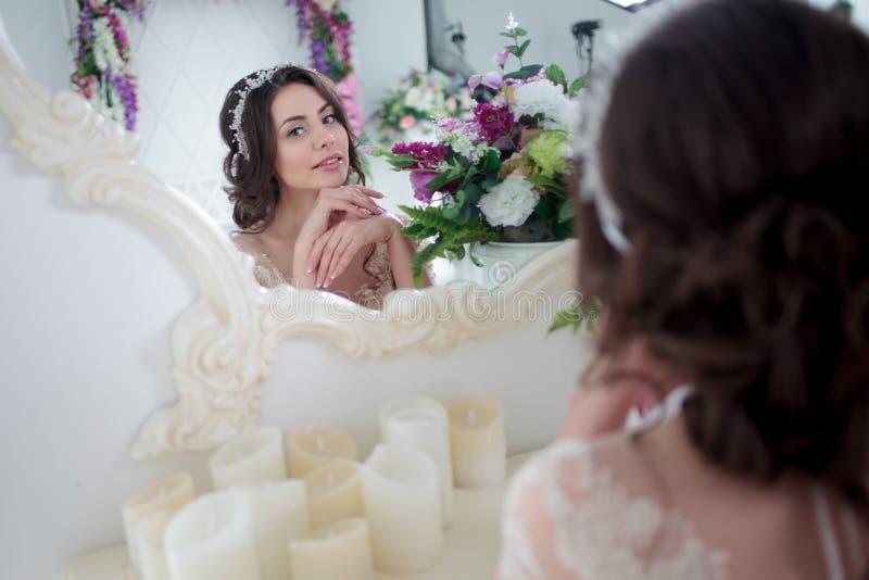 Jolie jeune femme dans la robe de mariage Se reposer contre le miroir photo stock