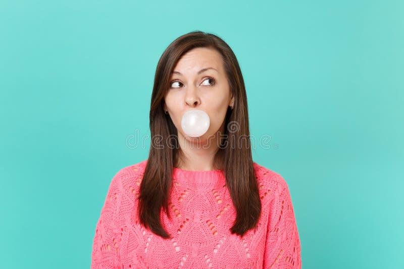 Jolie jeune femme dans le chandail rose tricoté recherchant, mâchant, ballon de soufflement de bubble-gum d'isolement sur la turq images stock