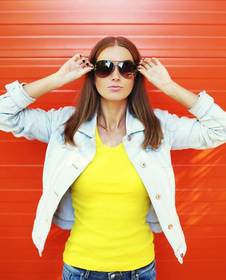 Jolie jeune femme dans les lunettes de soleil et la veste de jeans au-dessus de l'orange image libre de droits
