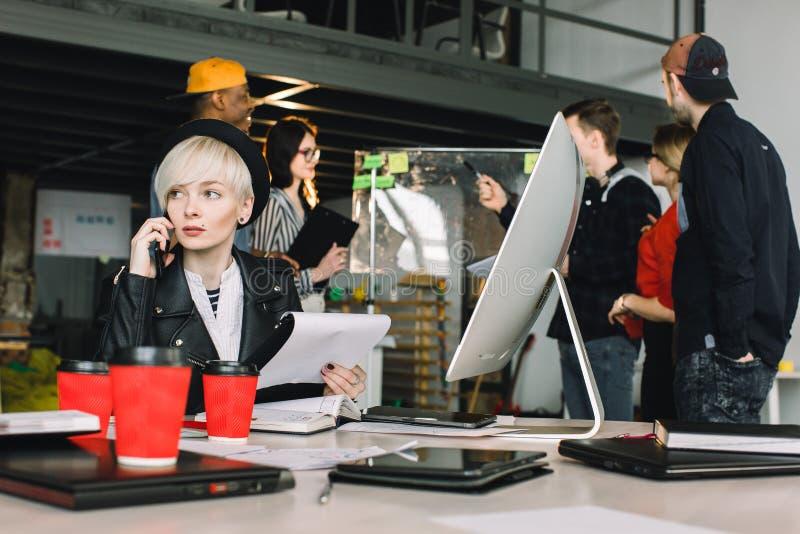 Jolie jeune femme dans les vêtements sport et le chapeau utilisant le téléphone tout en se reposant à la table dans le bureau de  photo libre de droits
