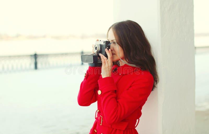 Jolie jeune femme de brune avec le rétro appareil-photo de vintage en hiver photos libres de droits