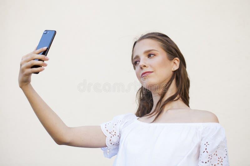 Jolie jeune femme de brune faisant le selfie sur le smartphone photographie stock libre de droits