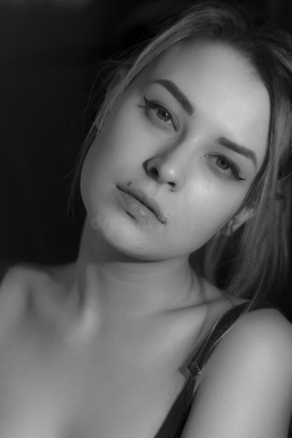 Jolie jeune femme de portrait noir et blanc dans le chandail sur le fond noir Regarder l'appareil-photo d'intérieur photo libre de droits