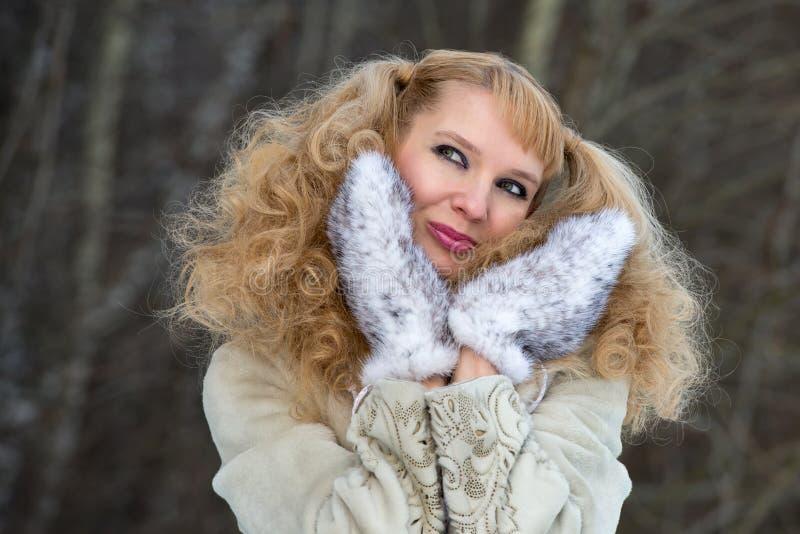 Jolie jeune femme de sourire dans un manteau de fourrure photo libre de droits