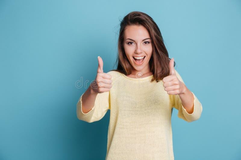 Jolie jeune femme de sourire montrant des pouces  image stock