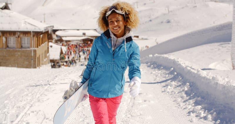 Jolie jeune femme de sourire portant un surf des neiges photo stock