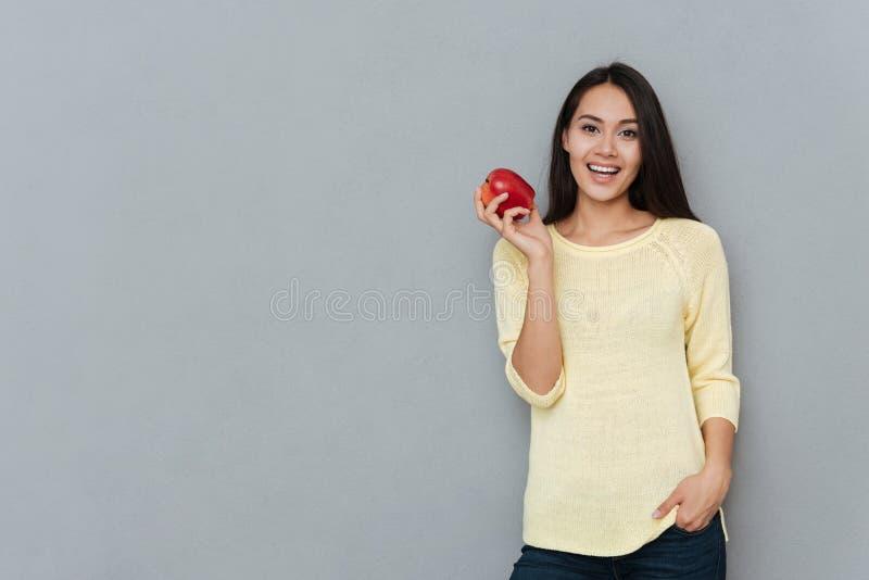 Jolie jeune femme de sourire tenant et tenant la pomme rouge photos libres de droits