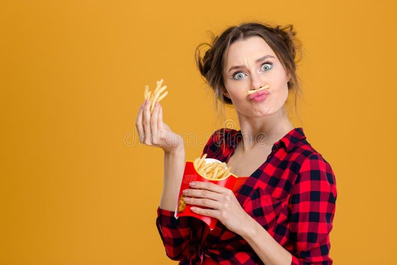 Jolie jeune femme drôle faisant la fausse moustache avec des fritures images libres de droits