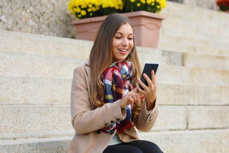 Jolie jeune femme en train de taper du doigt sur un smartphone, assise sur des escaliers, portant un manteau et une écharpe en hi image stock