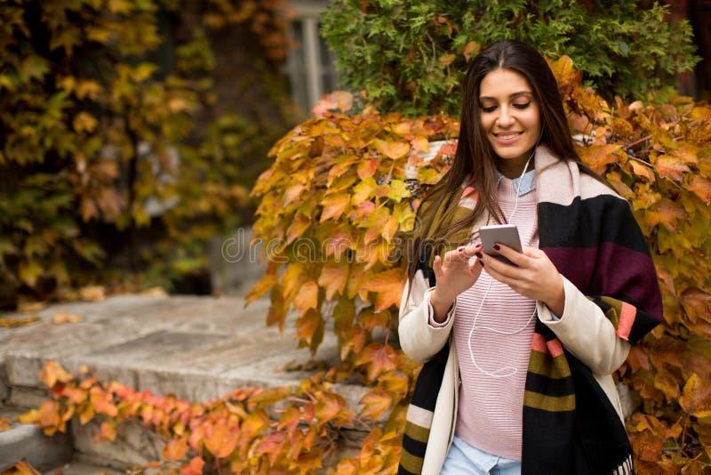 Jolie jeune femme extérieure avec le téléphone portable photo libre de droits