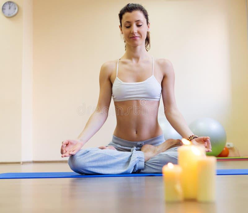 Jolie jeune femme faisant l'exercice de yoga sur le tapis image stock