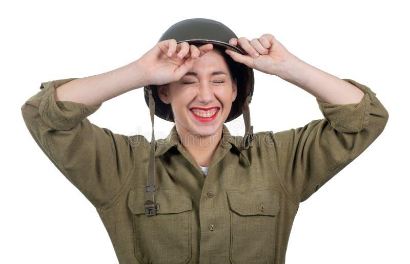 Jolie jeune femme habillée dans l'uniforme militaire de l'Américain ww2 avec le casque M1 photographie stock