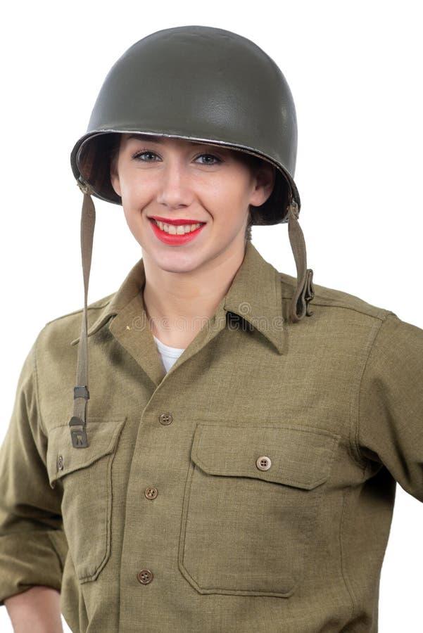 Jolie jeune femme habillée dans l'uniforme militaire de l'Américain ww2 avec le casque M1 images stock
