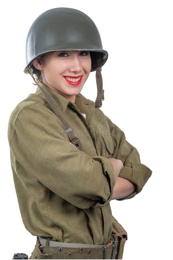 Jolie jeune femme habill?e dans l'uniforme militaire de l'Am?ricain ww2 avec le casque M1 photographie stock libre de droits