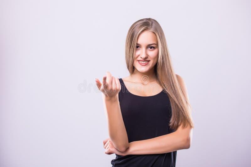Jolie jeune femme heureuse se tenant et se dirigeant à l'appareil-photo au-dessus du fond gris photo libre de droits