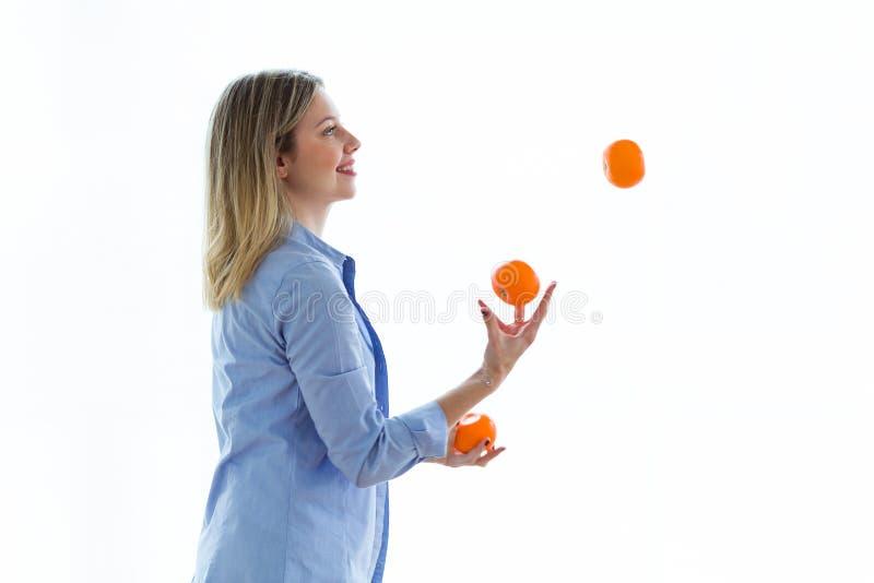Jolie jeune femme jonglant avec des oranges au-dessus du fond blanc images libres de droits