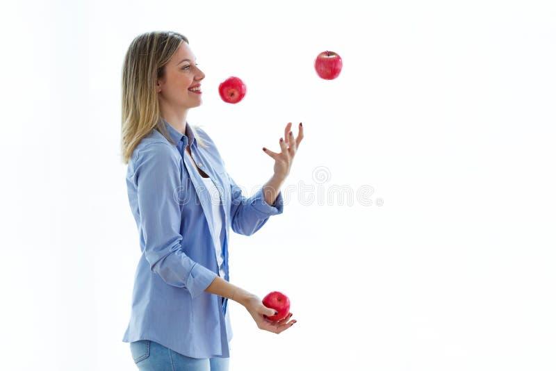 Jolie jeune femme jonglant avec les pommes rouges au-dessus du fond blanc image stock