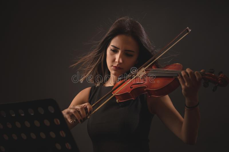 Jolie jeune femme jouant un violon au-dessus de fond noir photo libre de droits
