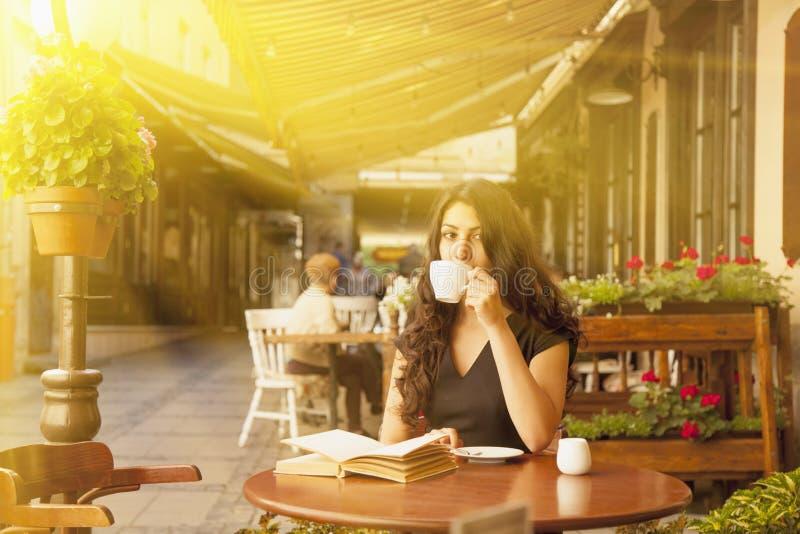 Jolie jeune femme lisant un livre et buvant du café à un ensoleillé photos libres de droits